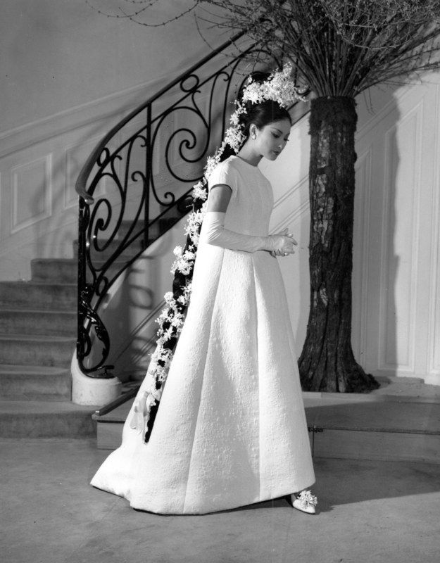 French designer Yves Saint Laurent's wedding gown in white damasked cotton is shown from his spring collection in Paris, France on Feb. 12, 1964. The dress is accessorized with white elbow gloves, shoes topped with flowers and a long tress trimmed with flowers