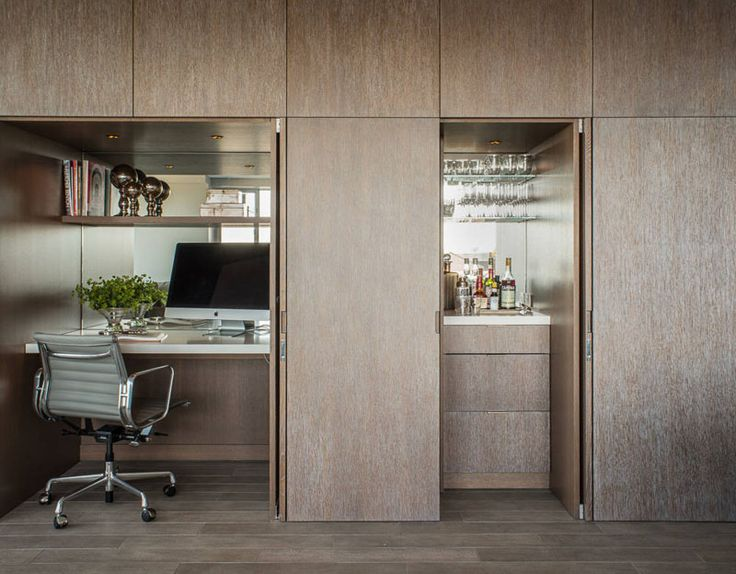 Small Apartment Design Idea - Create A Home Office In A Closet | When the doors are closed, this wall looks like a wall of paneled wood, but upon further inspection you'll find closet doors that open up to reveal an office and bar.