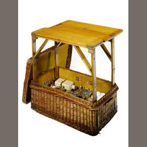 six person wicker picnic set with built-in table, by G.W. Scott & Sons, 1907,fine woven dark brown wicker cased, lined lid lifts off to reveal, fully fitted interior with ingenious mechanical fold-out table in light coloured oak, with two hinged leaves and the four cantilever support legs, which are neatly stowed under the table and lock into position when raised to form a solid surface, one leg has the original GWS ivory cartouche English patent plaque ' Patent 14907 ' for 1907....