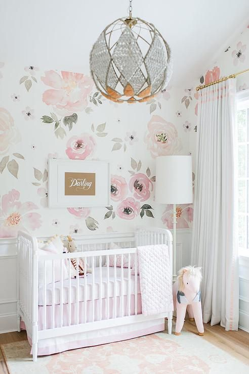 Adorable pink and white girl's nursery clad in Jolie Wallpaper on the upper walls and wainscoted lower walls features a Jenny Lind Floor…