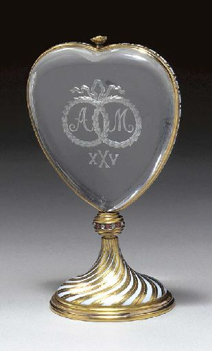 A JEWELLED GOLD AND ROCK-CRYSTAL WEDDING ANNIVERSARY MOMENTO marked Fabergé, with the workmaster's mark of Michael Perchin, St. Petersburg, circa 1896. The heart-shaped rock-crystal engraved with the letters A and M surrounded by two ribbon-tied laurel wreaths and number twenty-five in Roman characters.Gold frame designed with white opaque enamel, mounted onto a circular gold stand with alternating white enamel and gold spiralling bands terminating at a rose-cut diamond and ruby set collar.