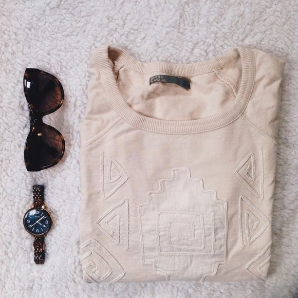 """Sfera Tribal Top Cream short sleeve top. Similar to sweatshirt material. Tribal design on front, sleeves cuffed with buttons, drawstring detail at hip. Purchased at department store in Spain. Worn once, mint condition.   Condition: Gently worn. Worn once.   ◆If you'd like more pics or have questions, ask! ◆If you'd like to make an offer, please use """"Offer"""" button. 🚫NO TRADES🚫 Sfera Sweaters"""