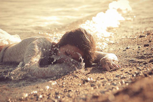 A mulher na praia parecia estar morta, mas a sutil movimentação de seu tronco me fez concluir o contrário.
