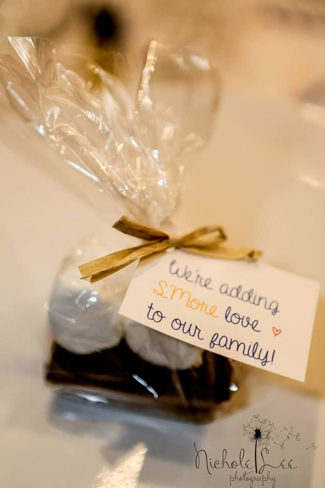 """We're adding s'more love to our family,"" S'mores baby shower favors. I made these using 2 graham crackers (its best to buy the ones that are pre-cut), 1/2 a full-sized Hershey's bar, and 2 marshmallows. Wrap in clear plastic bag, and tie with raffia ribbon."