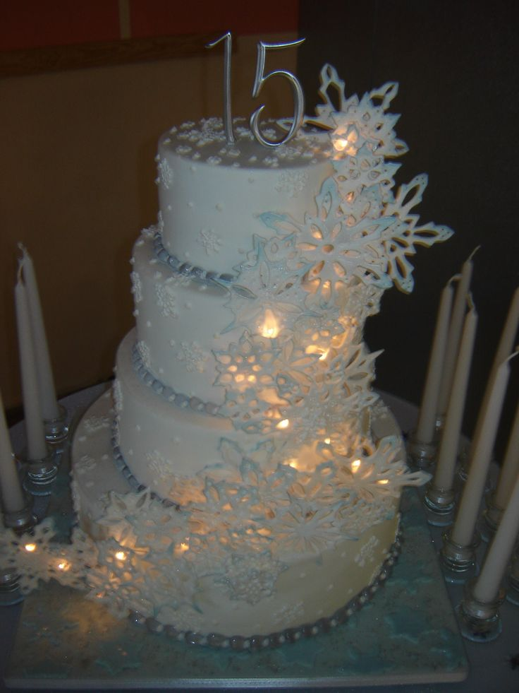 Snowflake tiered cake - Butter and white cake layers,buttercream. Snowflakes Tylose gumpaste recipe. Board decorated with fondant.  Quince (sweet 15) celebration