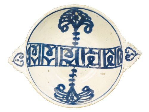 A rare Nasrid blue and white pottery eared cup, Spain, 15th century of deep round form with two scalloped handles, decorated in blue against a cream ground with a calligraphic band across the centre, flanked by two stylised palm tree motifs, the handles with outlined heart designs 20cm. max. diam. including handles.