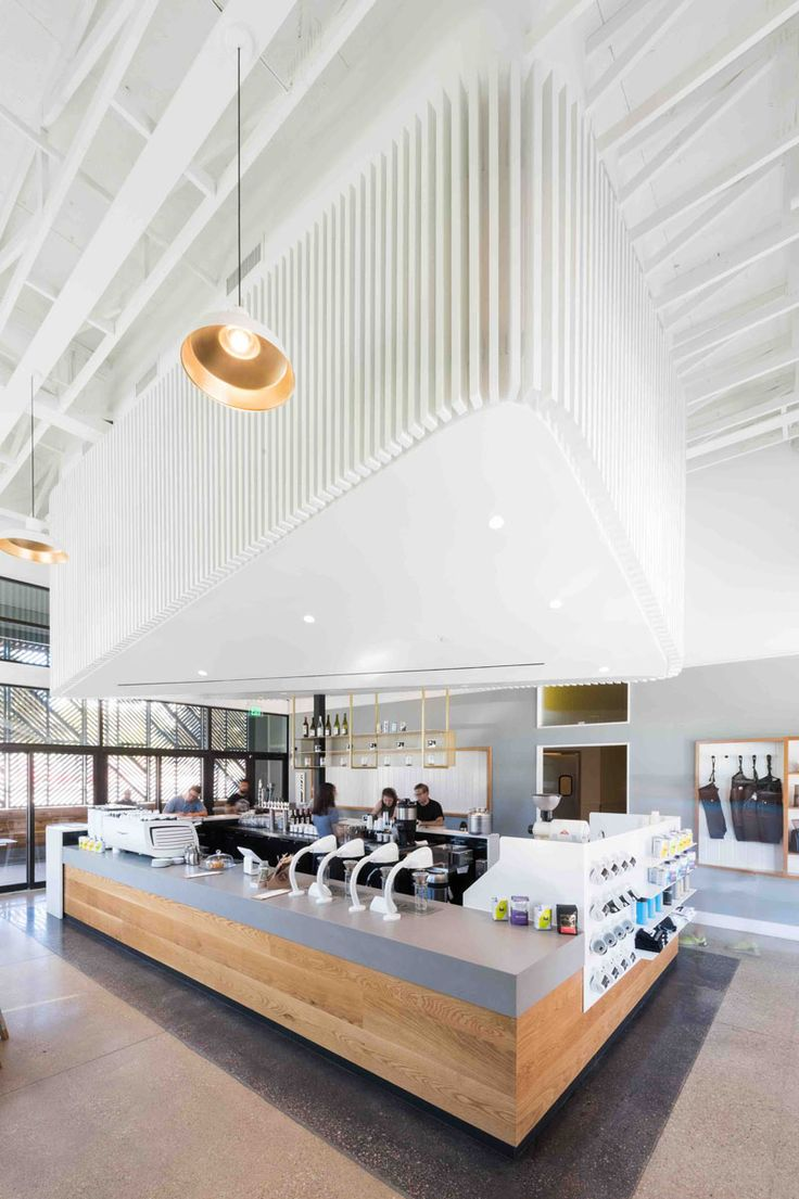 Inside this modern coffee shop, the interior is bright white and the high ceilings help to create a sense of openness. A 'cloud' that's positioned above the service bar draws your eye upwards and creates a focal point in the space, while at the same time, it hides the mechanical system.