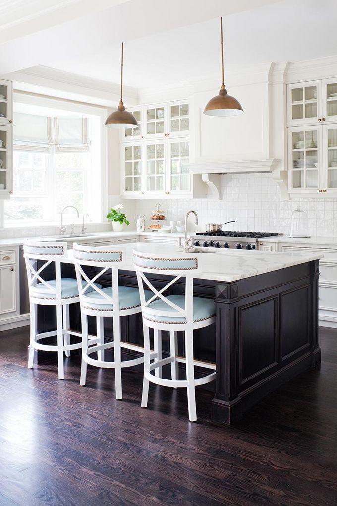 nailhead trim stools, dark floors and island, white glass cabinets ♥