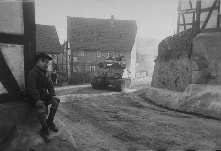 A young German boy sits beside the road as a tank of the U.S. 9th Armored…