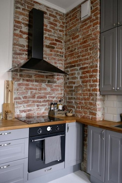 czerwona cegła na ścianie, czarny okap i szare szafki kuchenne