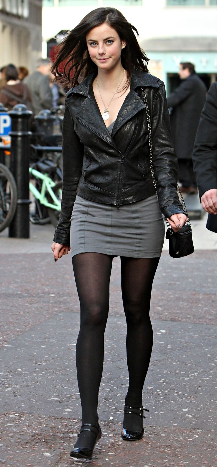 Kaya Scodelario black leather jacket, gray minidress and black strappy heels