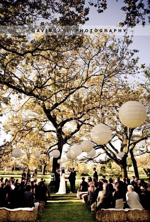 I love this with the paper lanterns and the hay bails.Wedding Canopy & Arches - Make the most of nature and seat your guests under a beautiful tree with several large white lanterns hung from it's branches.  #Wedding #Altar #WeddingCanopy  #WeddingArch #Ceremony