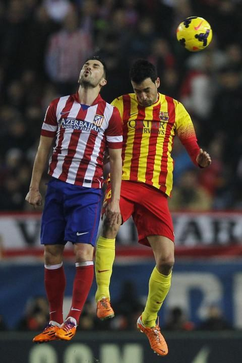 Barcelona's Sergio Busquets, right, in action with Atletico's David Villa, left, during a Spanish La Liga soccer match between Atlet...