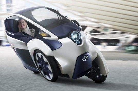 Toyota just unveiled its new i-ROAD concept – an all-electric three-wheeled trike that is set to debut this week at the Geneva Motor Show. Toyota says that the two-seater i-ROAD is the perfect vehicle for city streets. It offers the same low running costs, easy parking and around-town maneuverability as a motorcycle or scooter, but its fully enclosed interior makes it a safer alternative.