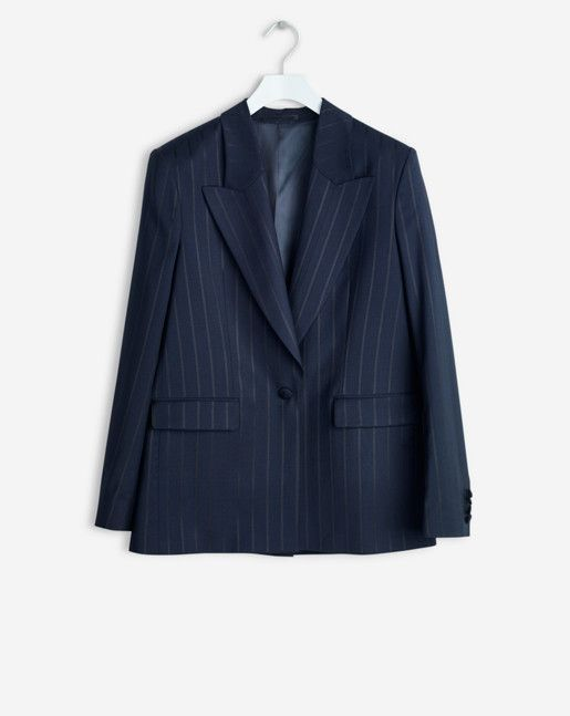 A slightly oversized and longer jacket in  navy cool wool with a shiny wide black pinstripe. Distinct wider collar and lapel. One button. A masculine style in a sophisticated material.