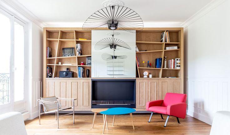 Salon avec bibliothéque et luminaire sur-mesure réalisé par un architecte d'intérieur à Paris