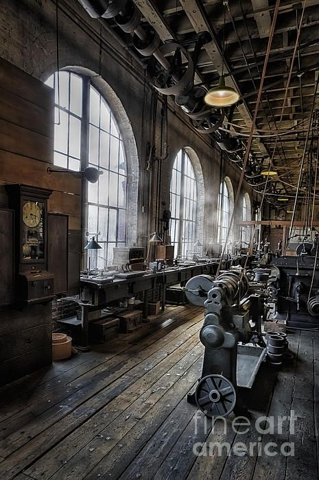 An antique machine shop showing heavy machinery, the belts that powered the machines, as well as an old fashioned time clock where employees would punch in and out to keep track of the hours they worked.
