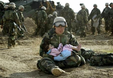 Une petite fille tenue par un soldat américain, après s'être séparée de sa famille pendant la guerre en Irak.