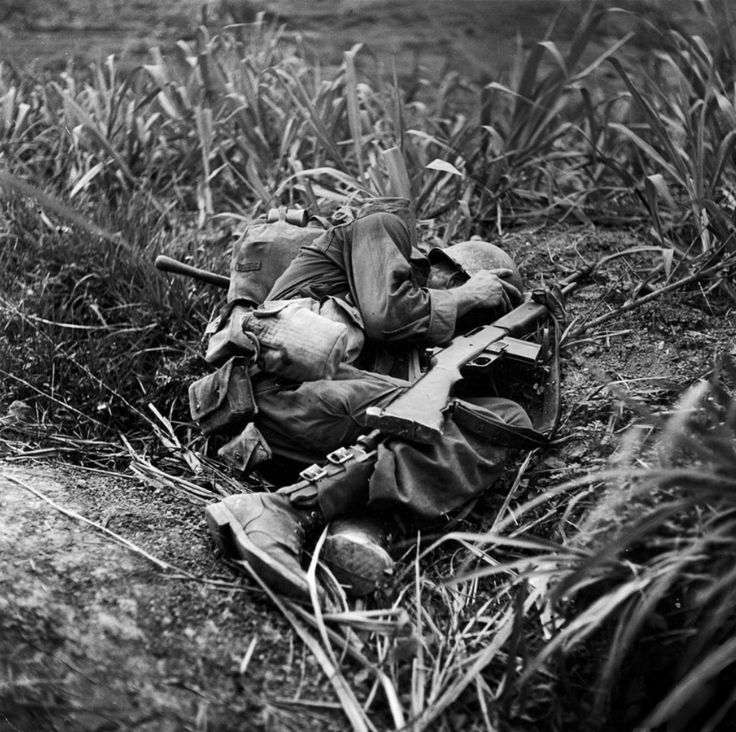 "U.S. Army infantryman, Pfc. Terry Moore of ""F"" Company, 184th Regiment, 7th Infantry Division, takes cover as incoming Japanese artillery fire explodes nearby during the fight to take island of Okinawa during the Battle of Okinawa (Operation Iceberg). Moore survived with severe injuries to his face and hand. Okinawa, Okinawa Prefecture, Ryukyu Islands, Japan. June 1945. Image taken by W. Eugene Smith."