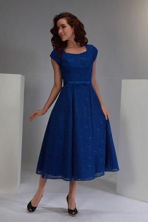 gorgeous style! Lace over matching cobalt lite satin dress with square neckline and petal sleeves. Satin band with bow on waist. Box pleated skirt.