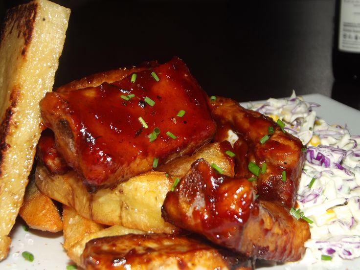 Costillas de cerdo marinadas y cocidas lentamente al vació por 12 horas en BBQ casera acompañado de papas crocantes caseras y ensalada de repollo morado.