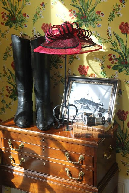 Framed vintage photo of Churchill Downs, antique tortoiseshell viewing binoculars, a Derby Day hat, riding boots and trophies in the entry hall at the Kentucky Derby Party. Photo credit: thepolohouse.blogspot.com ..