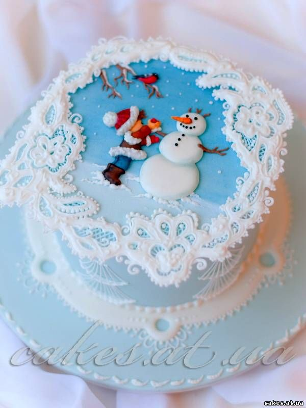 Royal icing lace collar against icy blue background; winter scene with child and snowman. Beautiful.