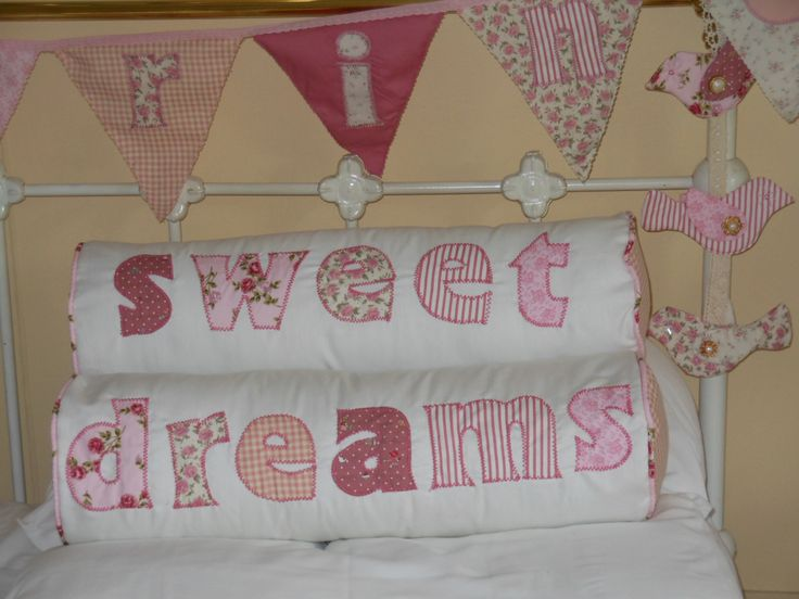 "Pretty bolster cushions with appliqued words in pinks.  ""Sweet Dreams"" combined with hanging birds and bunting.  Every little girl's sweetest dream to have a room decorated in pink."