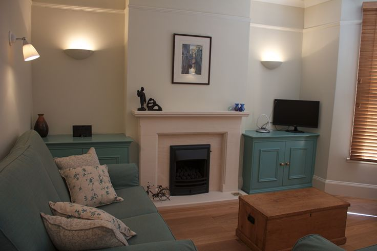 A new limestone fireplace and built in cupboards painted in Farrow  Ball's Dix Blue