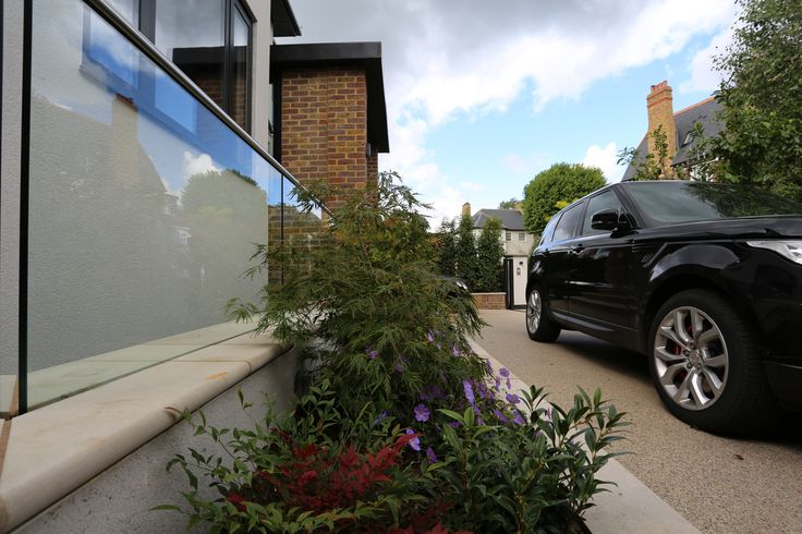 Contemporary garden landscaping in Richmond  Paving: Black Basalt from London stone Black Basalt steps and coping with London stone Lawn: Arena Gold turf Everedge Pro and porcelain strip mowing edging Water feature, irrigation system, stainless steel slot drain, etc.  Positive Garden Ltd