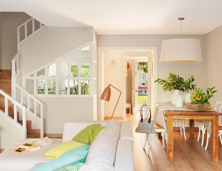 Hacia la escalera pared acristalada con cuarterones de madera blanca