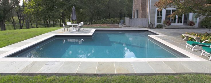 With a bold and contemporary style, this renovation incorporates soft color throughout the design with subtle shades of gray. A dark waterline tile surrounds the edge and reflects sharply into the water. The dark plaster gives the pool water a deeper blue coloring. Crisp edges are created by the coping and offset by the organic surface texture of the decking.