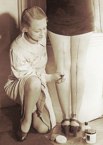"1940's~This woman is painting a line on the back of the other woman's leg to look like she is wearing nylons. Popular ""back in the day""!"