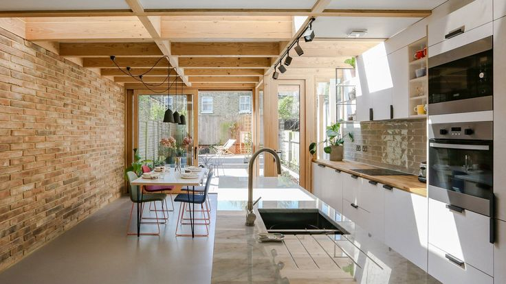 Timber portals frame large windows and skylights in this extension, which Nimtim Architects has added to the rear of a terraced house in Peckham