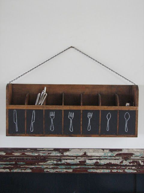 Free up your cupboard drawers by storing your eating utensils, candles, and napkins in a wall-mounted divided shelf. For versatility, label each cubby with a square of chalkboard paint. Hang the shelf in an easy to reach, well traveled portion of your kitchen.