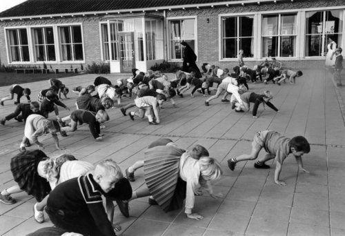 Op de speelplaats van een christelijke lagere school wordt [als gymles] een spel   gespeeld waarbij de schoolkinderen op handen en voeten lopen, 1960.