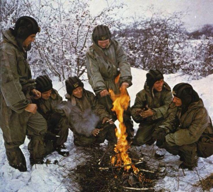 Czechoslovak People's Army tankmen taking a break around a fire during winter maneuvers.