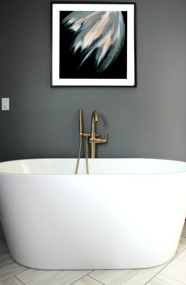 This bathroom remodel is gorgeous. It's a great combination of masculine and feminine design perfectly balanced. Black, Gray, and Brass Master Bathroom Remodel   Dark Gray Walls   Art above Bathtub   Brass Fixtures   Brass Bathtub Faucet   Oval Freestanding Bathtub