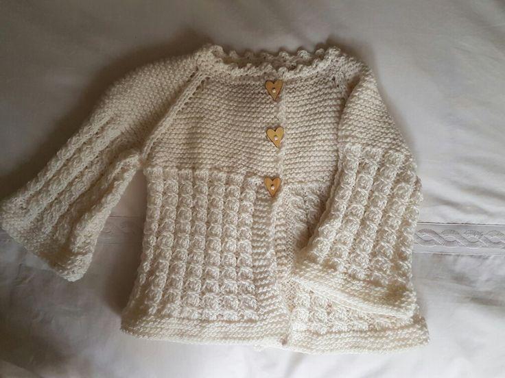 Chaleco tejido niña con dos agujas lana blanca y botones de corazón. Terminaciones en crochet