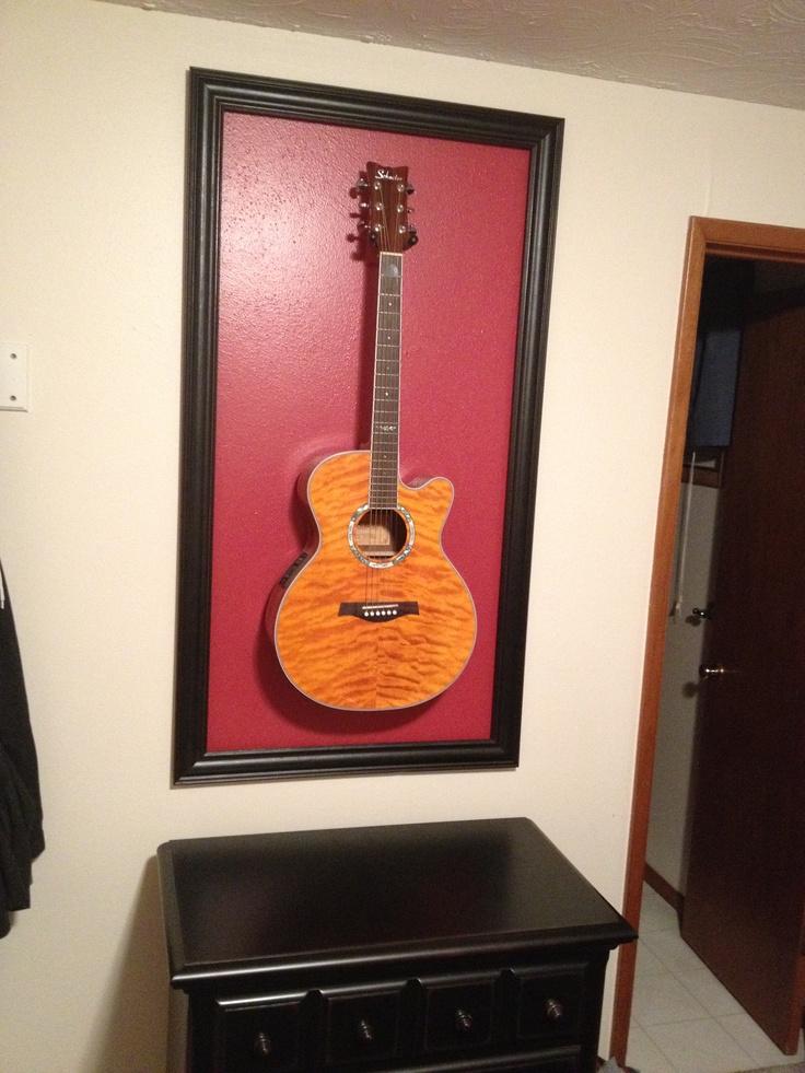 Very proud of myself for thinking up this cool way to display a guitar like a work of art!  Painted a square on the wall and hung  an open frame around it, then hung the guitar!