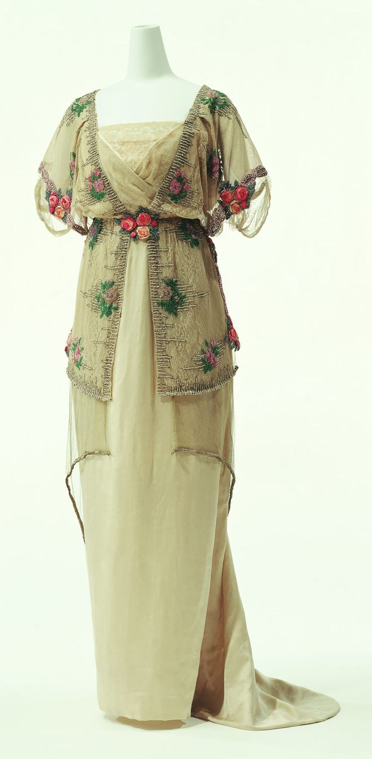"Evening Dress, Paul Poiret: 1910-1911, silk satin dress with silk tulle overdress, embroidery of beads and metallic thread, tulle peplum. ""...In 1906, when the S-curve silhouette was still overwhelmingly popular, Poiret introduced high waist corsetless dresses. He shifted the fashion trend substantially from 19th-century dresses in artistic forms with excessive decoration toward innovative clothing that accentuated the natural beauty of the human body..."""