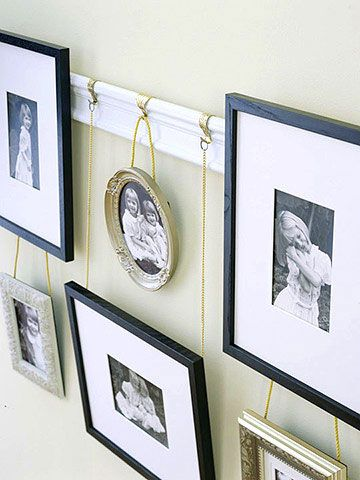 DIY Photo Album Display.. It's like a photo album for your wall! We modified a piece of common molding to make a picture rail. Decorative golden picture hooks fitted with short lengths of hardware-store chain suspend all sizes and shapes of frames. Simply cut the chain to the desired length and top with a circular link. Then hang each piece and enjoy happy memories each time you pass by.