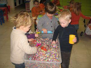 ontdekbak met confetti, serpentines, en andere carnavalsspulletjes. Ook bekertjes en andere recipiënten om met de confetti te experimenteren