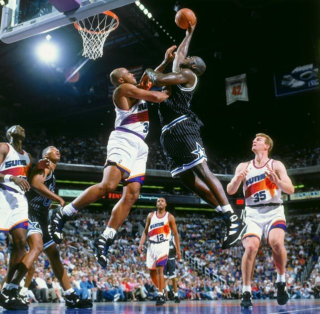 Shaquille ONeal of the Orlando Magic goes up for a dunk on Charles Barkley of the Phoenix Suns during a game in 1994.