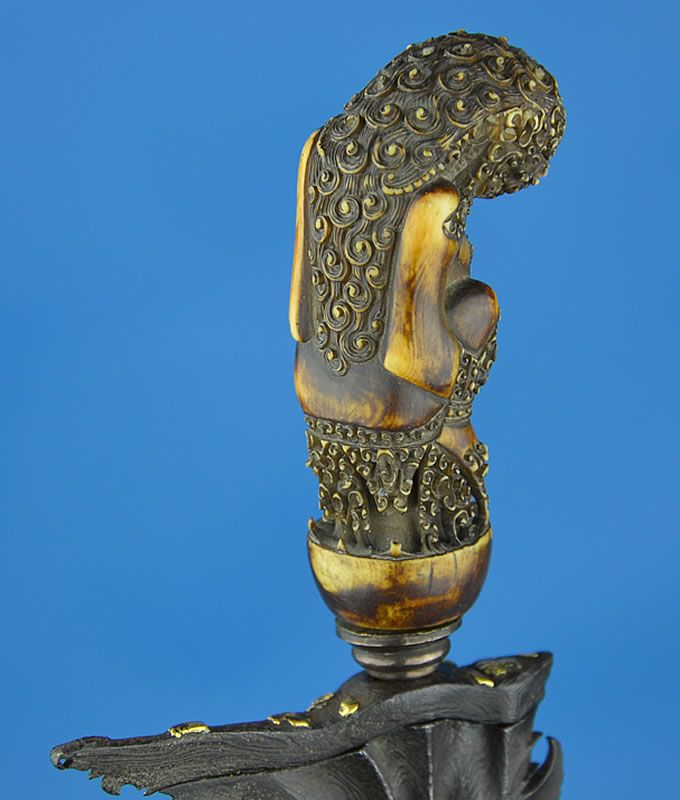 A fine and early Kris, or Keris, dagger from Java, Circa 17th Century. The wonderfully carved ivory hilt is in the form of a crouched Bhima or Garuda. His hands rest on his legs, displaying two extremely long thumbnails. He has long curly hair, and a necklace of snakes. www.akaalarms.com