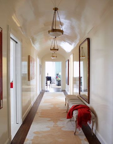 High Gloss Painting- The long vaulted hallway is brightened by light from windows in the surrounding rooms reflecting off the walls and ceiling. A bistro mirror adds illusory space. Three neoclassical alabaster ceiling lights hang above a Madeline Weinrib Orleans runner.