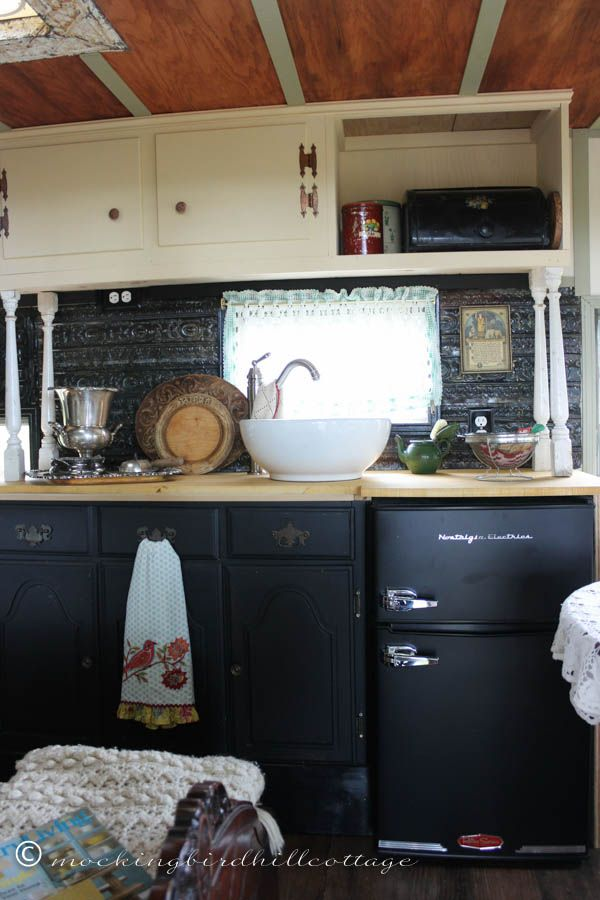 Dark painted cabinets, tin backsplash, wood floors. Nice trailer