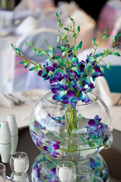 "Fill one of our 5"" Bubble Ball Vase (Bubble Bowl) one third full of water. Using blue and purple orchids place a stem or two, vertically inside the bowl with a small cylinder bud vase.  Create a bunch with several of the same orchids and set them in the center of the bowl."