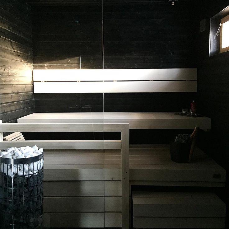 Vaaleat lauteet tuovat modernin tuulahduksen saunan tummille pinnoille. Huomaa myös valkoiset kiuaskivet.