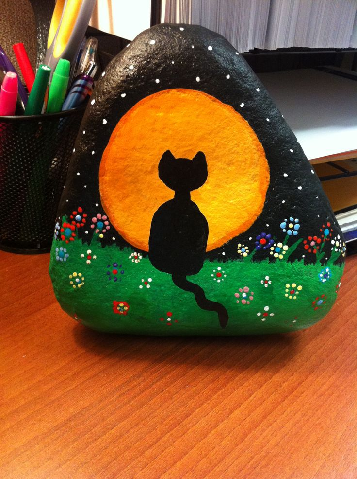 Black cat looking at the havest moon painted on a stone